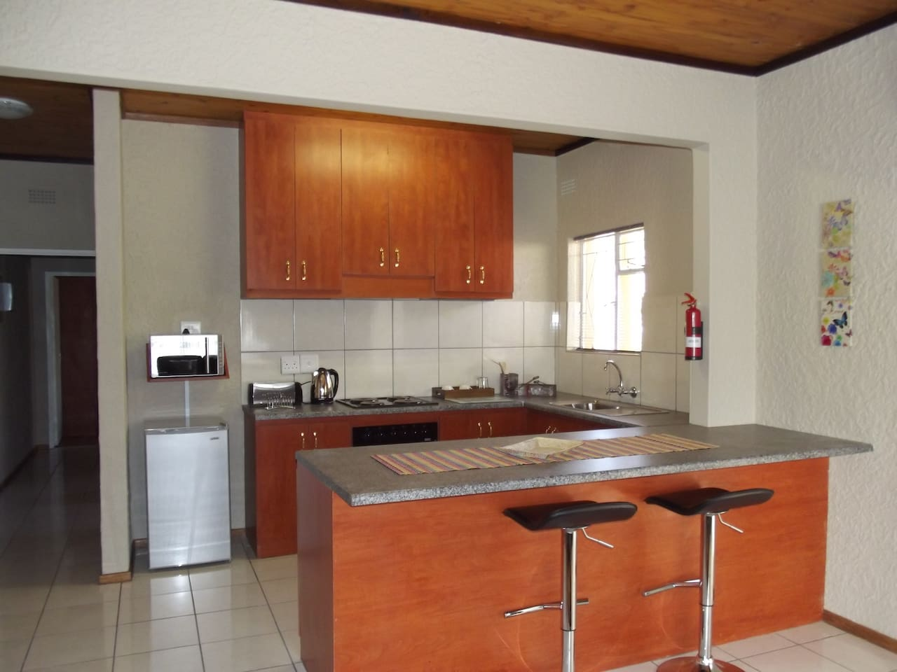Fully furnished kitchen with washing machine and tumble dryer.