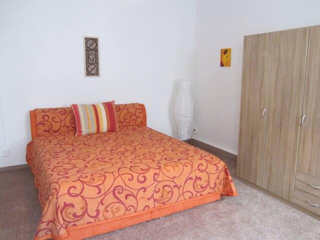 Das bequeme große Bett mit Kleiderschrank, inzwischen auch Nachttisch mit Lampe (vom Betrachter links)