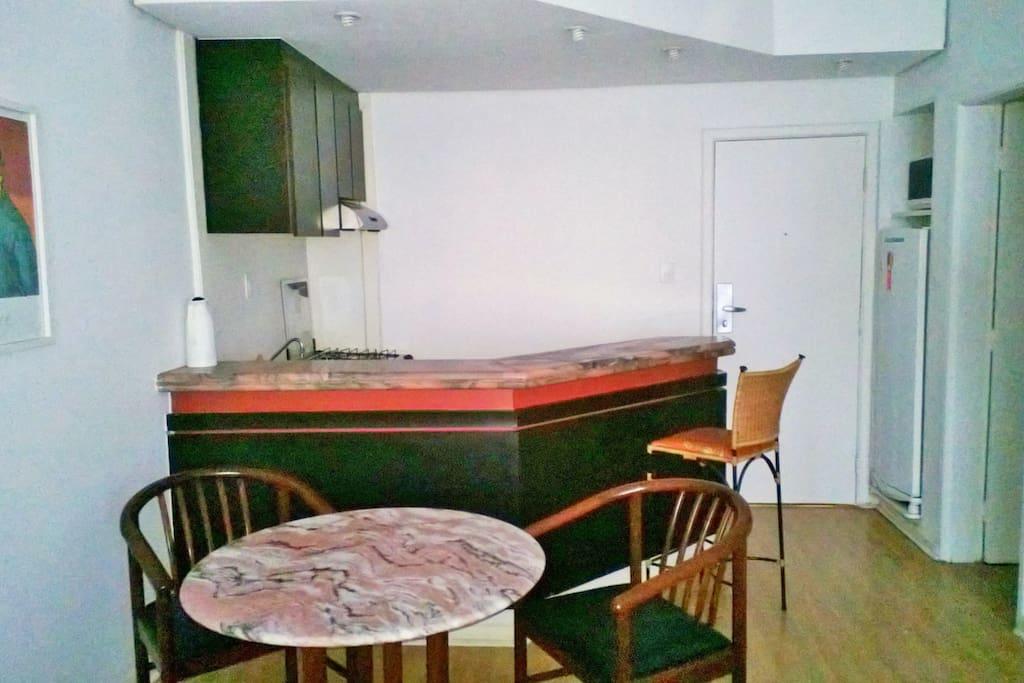 Vista cozinha americana, armários com louças, utensílios, geladeira, micro ondas, máquina café,  fogão, torneiras com água quente e fria.