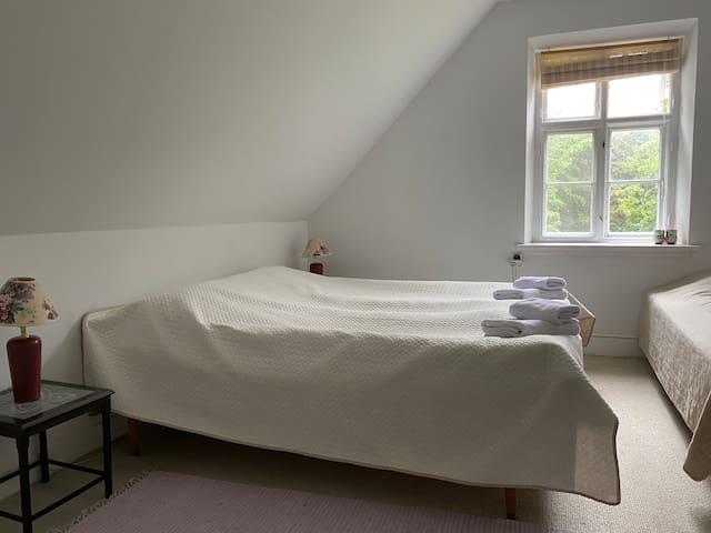 Room 1- double bedroom & single bed, garden view.