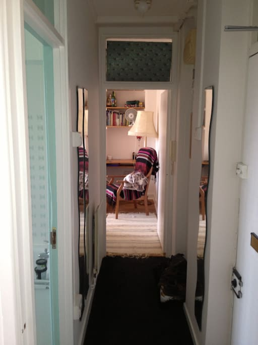 The entrance hallway facing the lounge -front door on the right and toilet on the left with the bedroom behind the camera