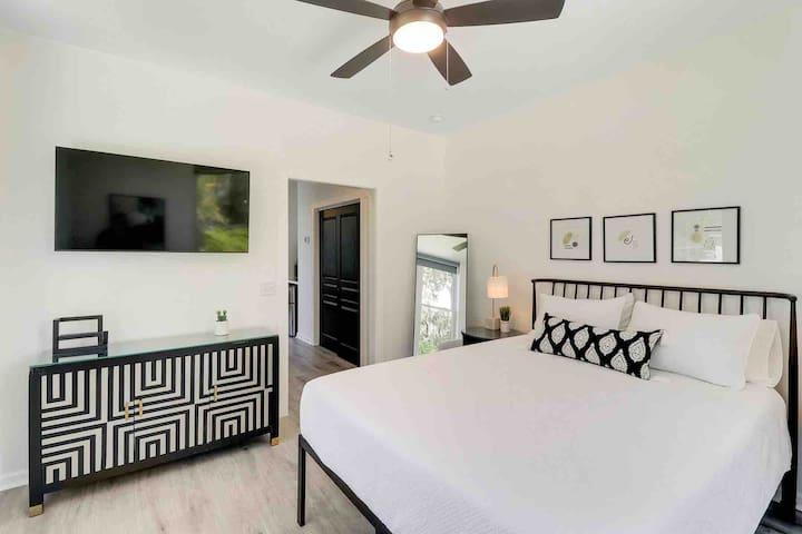 Bedroom worn queen bed and large smart TV