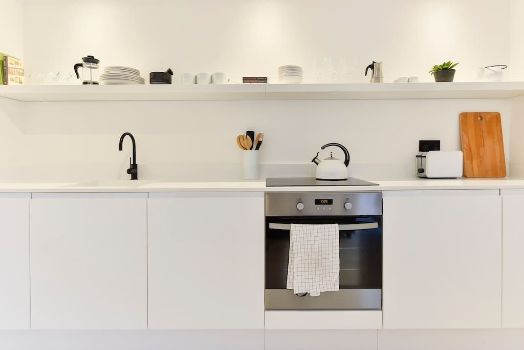 The clean, modern kitchen with oven and hob, fridge and dishwasher, toaster and kettle. Everything you need to cook up a tasty meal.