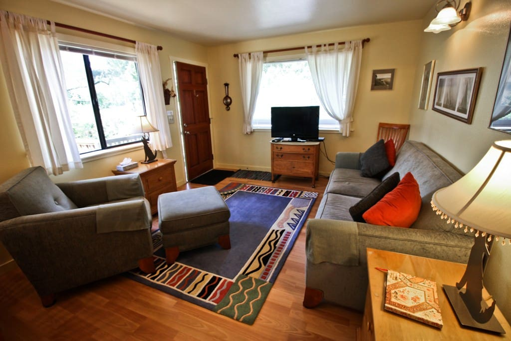 Living room with a flat screen cable TV/VCR/DVD player, couch, overstuffed chair with ottoman and ocean view