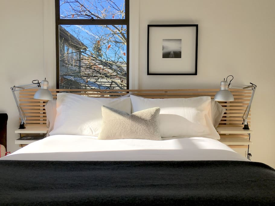 Comfortable queen size bed with reading lights and luxurious bed linens.