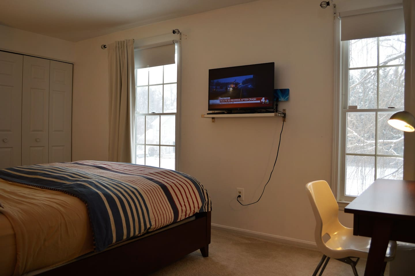 A modern bright clean room with two windows, A Flat-screen TV equipped with Chromecast TV and a comfortable working desk.