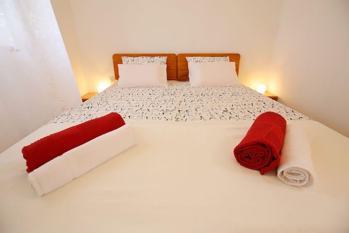 Spavaća soba s velikim bračnim krevetom 160 x 200.  Ako zatreba, na  raspolaganju vam je i rasklopivi dječji krevetić za bebe.