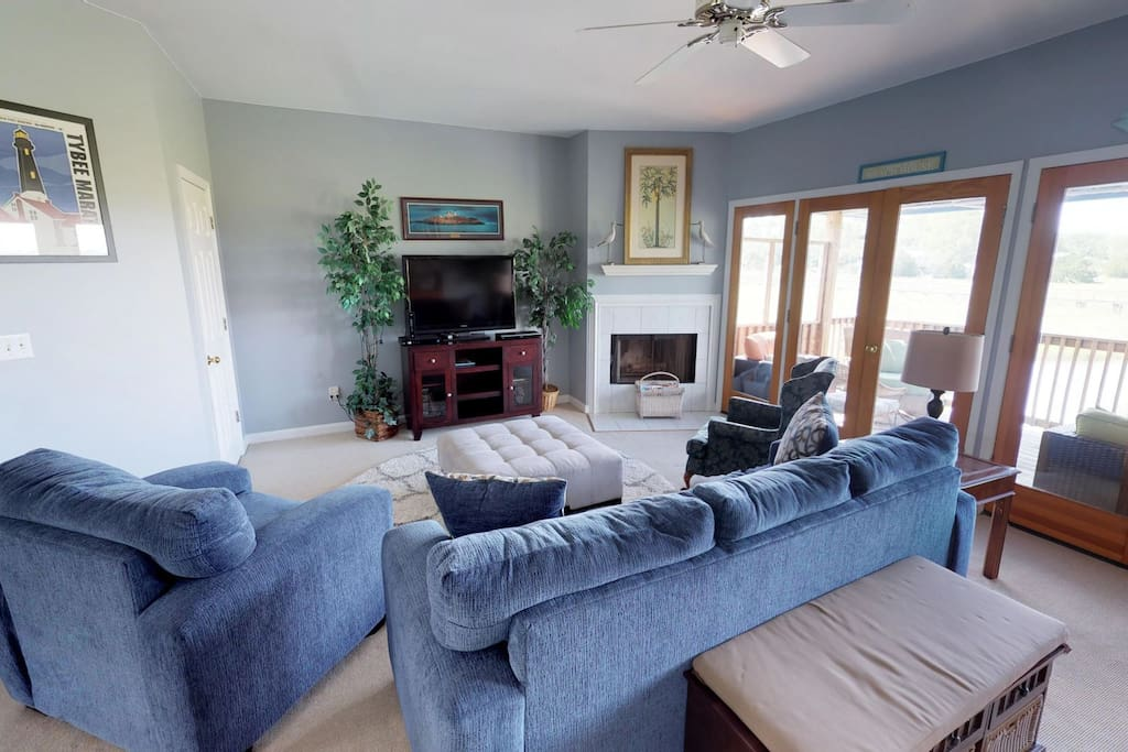 Spacious and comfortable living room with queen sleeper sofa, flat panel TV, and balcony access