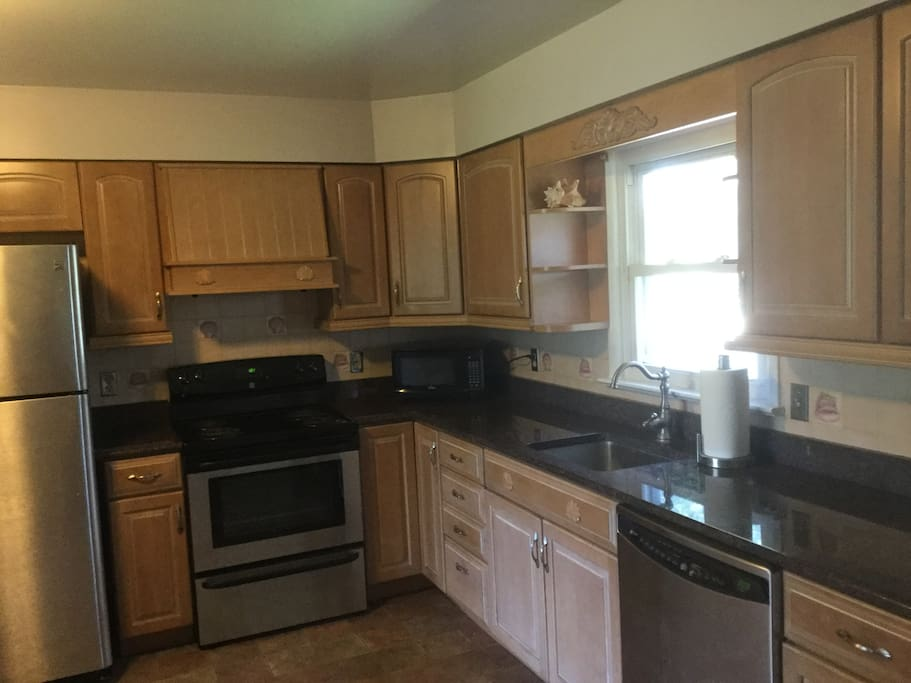 Spacious kitchen with granite counter tops and stainless steel appliances.