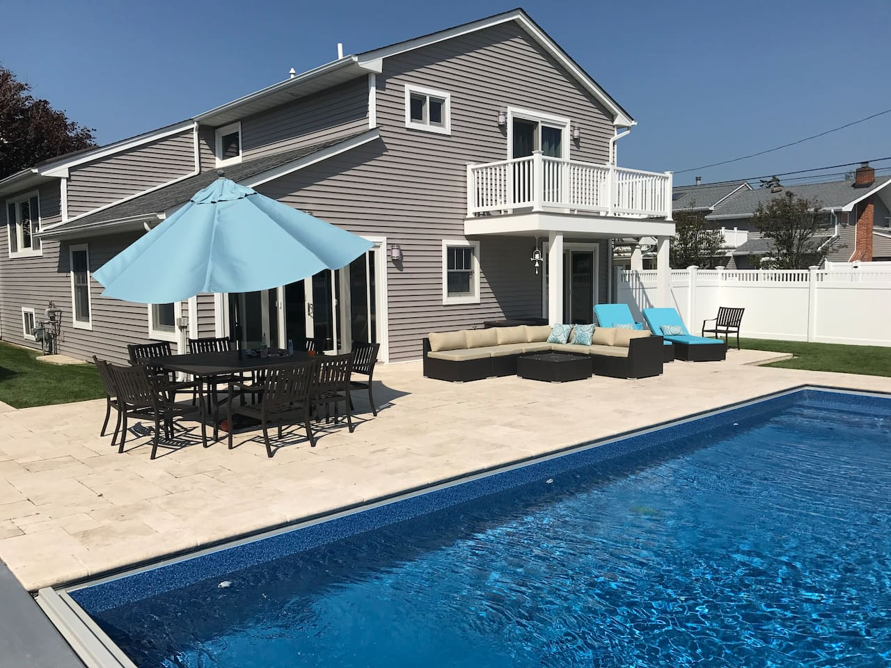 Heated in-ground pool surrounded by new patio, plenty of seating and lounging options