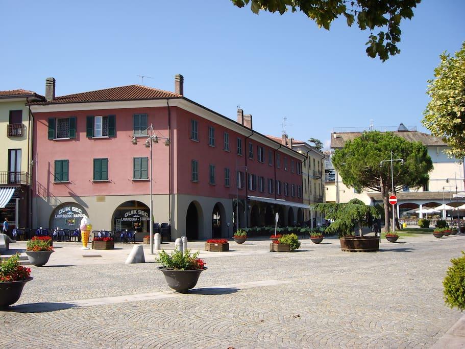 La piazza a lago di Colico con l'edificio in cui si trova l'appartamento
