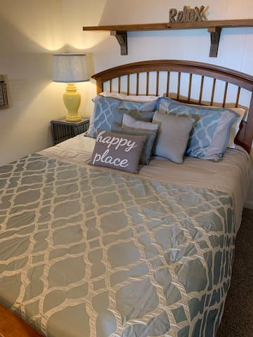 Another queen size bed with reading lamps, flat screen smart TV, and comfy side chair.