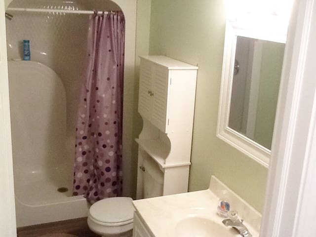 Clean bathroom with single vanity and large standup shower.