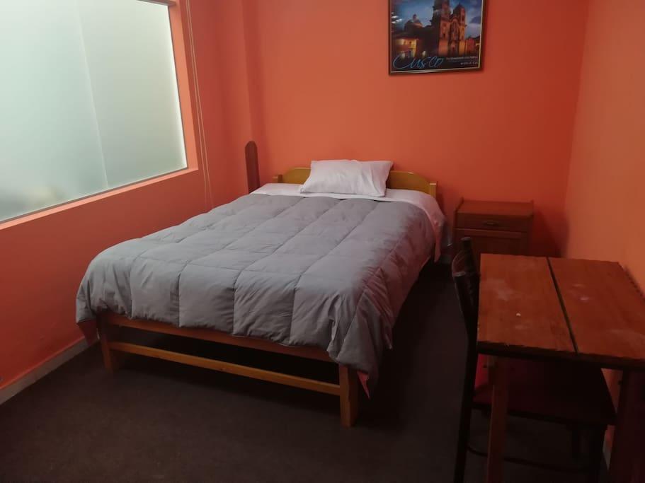 Habitación con baño privado, en primer piso con ropero, mesa y silla.