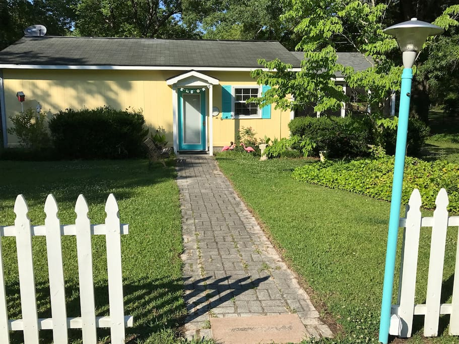 Sunny yellow cottage with picket fence greet you!