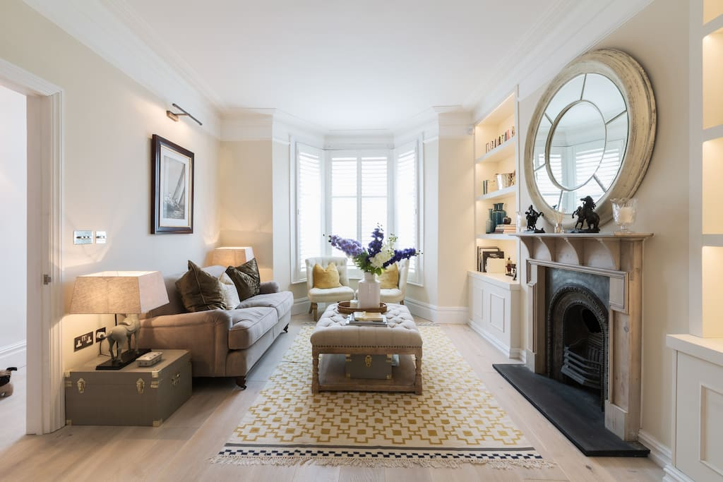 Our formal sitting room, a gorgeous bay fronted sitting room with Victorian fireplace, sofa, armchairs and shutters!