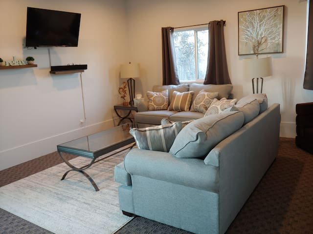 Clean, bright living room with comfortable couch and loveseat and TV with Firestick (Netflix, Amazon Prime, and Hulu available) and sound bar.