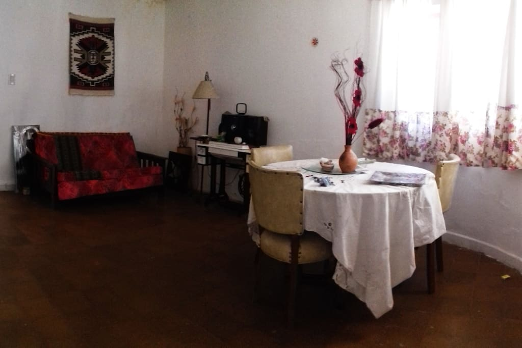 Sala privada anexa a la habitación, con mesa y sillón.