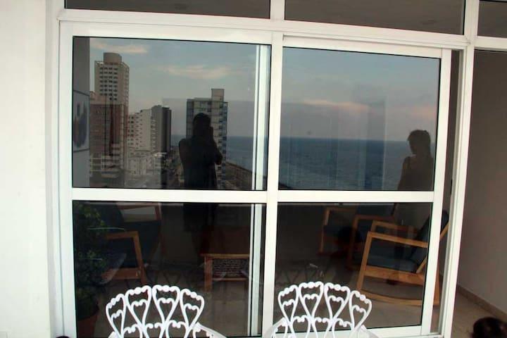 Sala vista desde la terraza con el mar reflejado en las ventanas.
