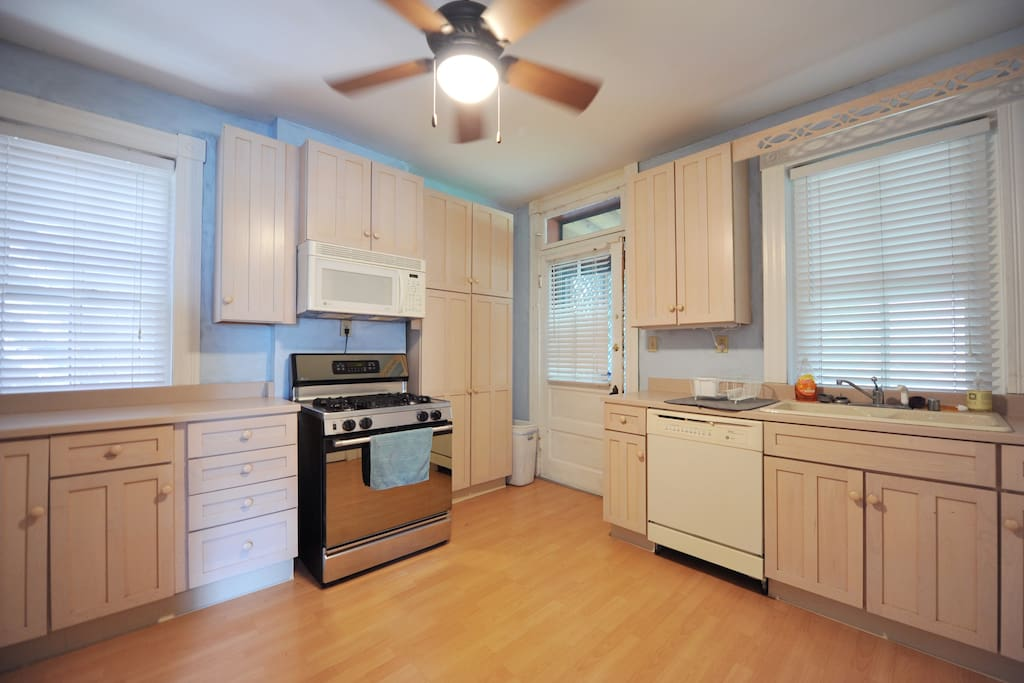 White washed cabinets with stainless steel stove. The door leads to a sunny screen-in porch as well as the cozy backyard.