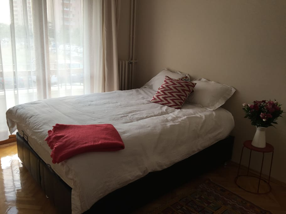 The bedroom which is cozy and simple.. The room is light with a small balcony.