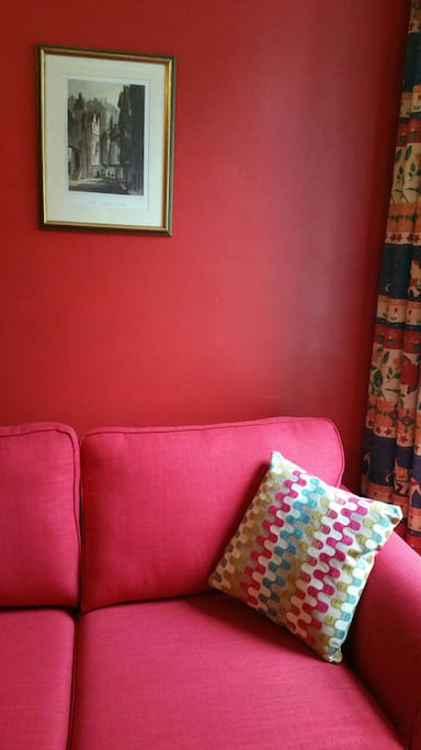 The red sofa bed. Which faces a wall mounted TV.