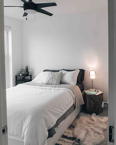 Beautiful comfortable and stylish bedroom that features a queen bed and storage. Lots of natural light and modern feel.