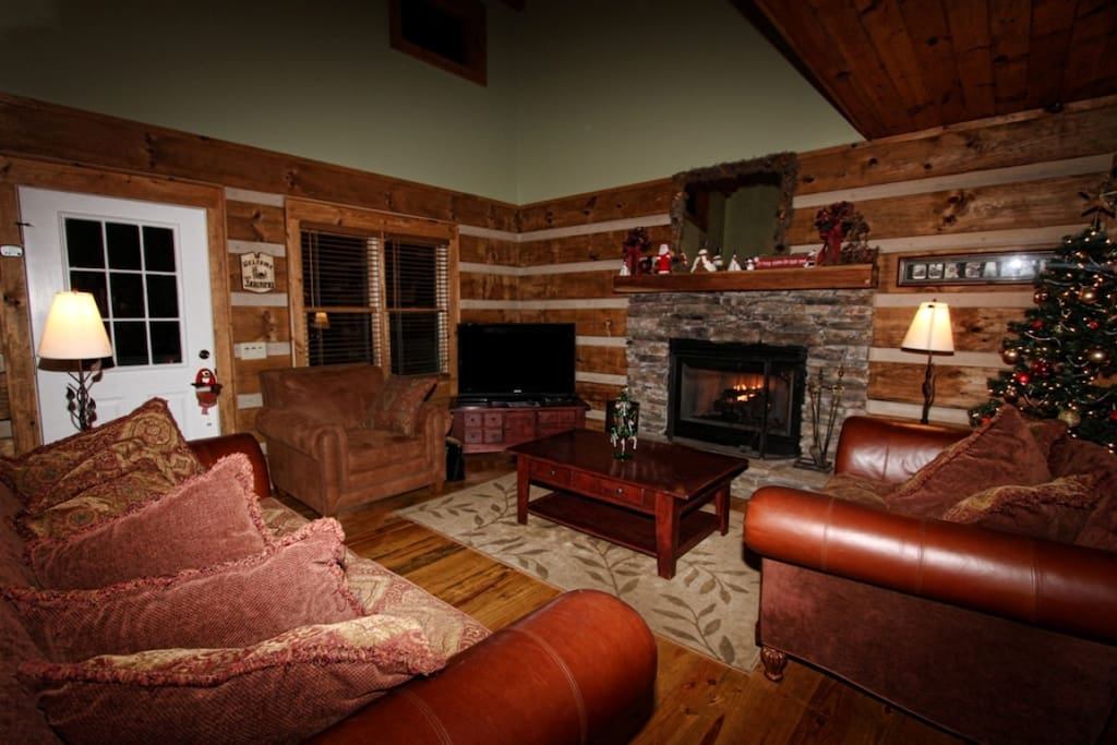 """Cozy living area surrounding hand-stacked stone hand-stacked stone fireplace and 50"""" HD television."""