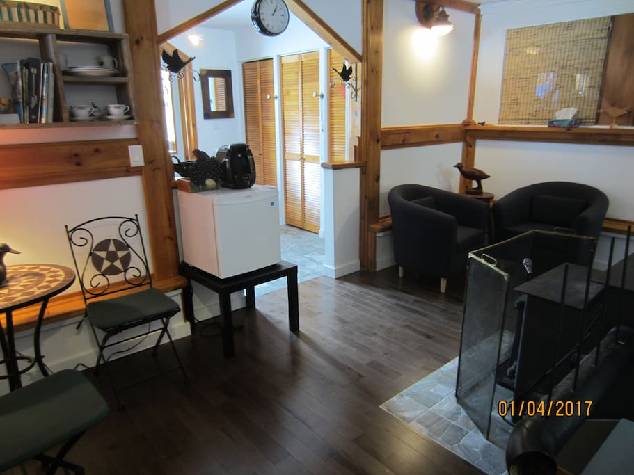 Salon attenant aux chambres avec une cafetière et frigo.