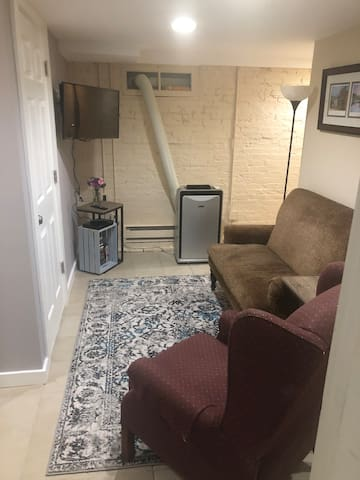 """Living space with satee, recliner, 32"""" tv, bluray player."""
