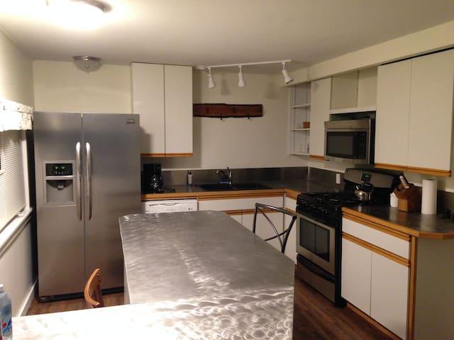 Modern kitchen with dishwasher, pots, pans, dishes, utensils