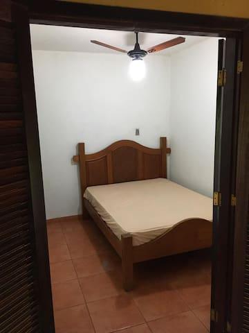 Quarto casal com uma cama de casal e ventilador de teto e banheiro próximo