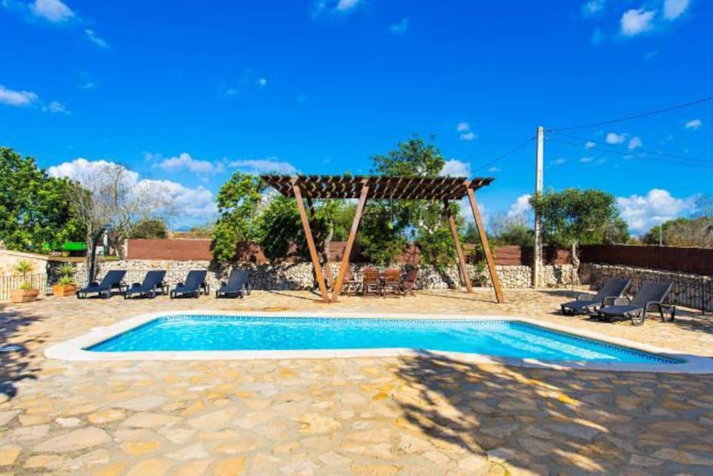 terraza piscina con comedor bajo la pérgola