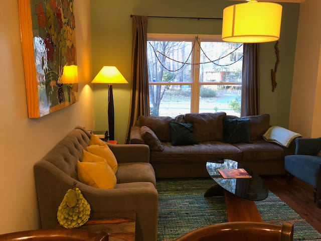 Sitting room off of kitchen is a roomy space to gather while keeping the cooks company.