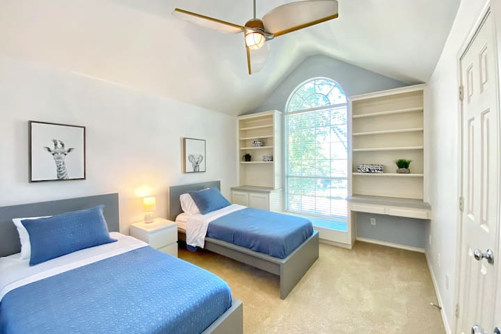 This room features two single beds and has a large window looking out on the tree-lined street.