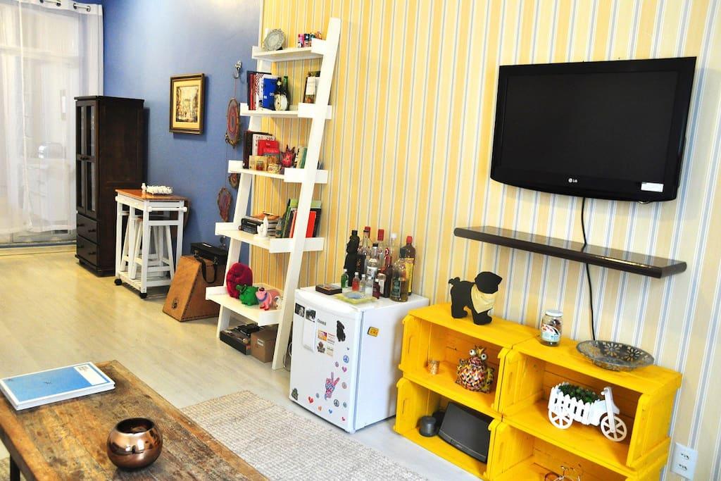 Frigobar disponível para uso, TV, decorações e móveis úteis na sala.