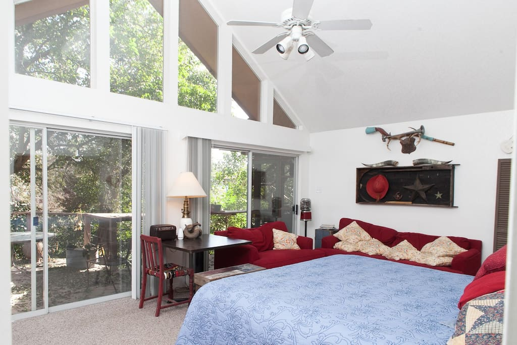 Large bedroom with king sized bed and sofas for lounging. Wake up to the sun rising over the Comal River.