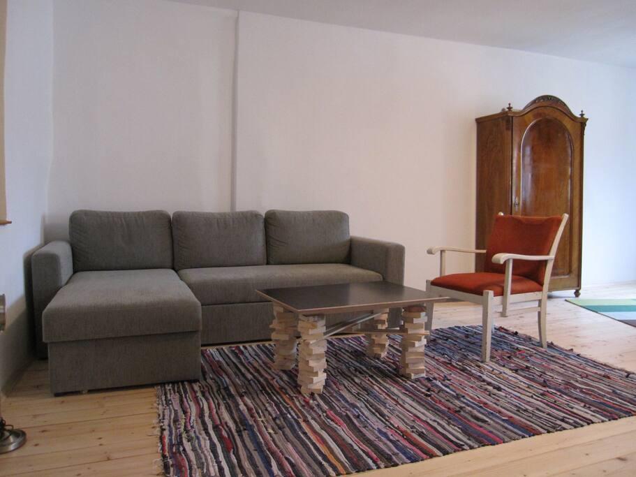 Die Couch im Wohnzimmer. Sie kann zu einem Doppelbett umgebaut werden.