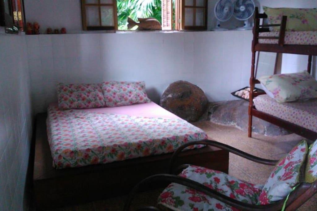 Suíte com a cama japonesa, beliche, cadeira de balanço e ventiladores.
