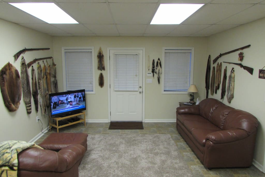 The den decor consists of  professionally tanned wildlife pelts & black powder antique rifles.