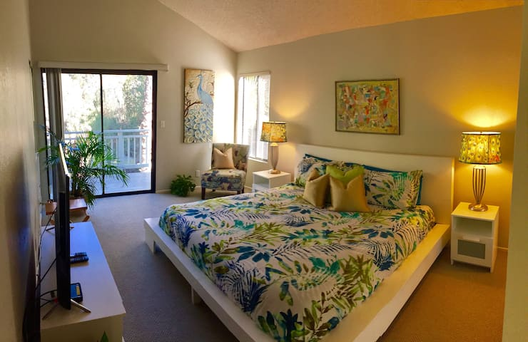 """Up Master Bedroom with vaulted ceilings, 4K flat screen TV, Copper lux memory foam King bed, private balcony with """"jungle"""" views and table and chair set on the balcony. Designer sitting chair and peacock lamp shades complete the look."""
