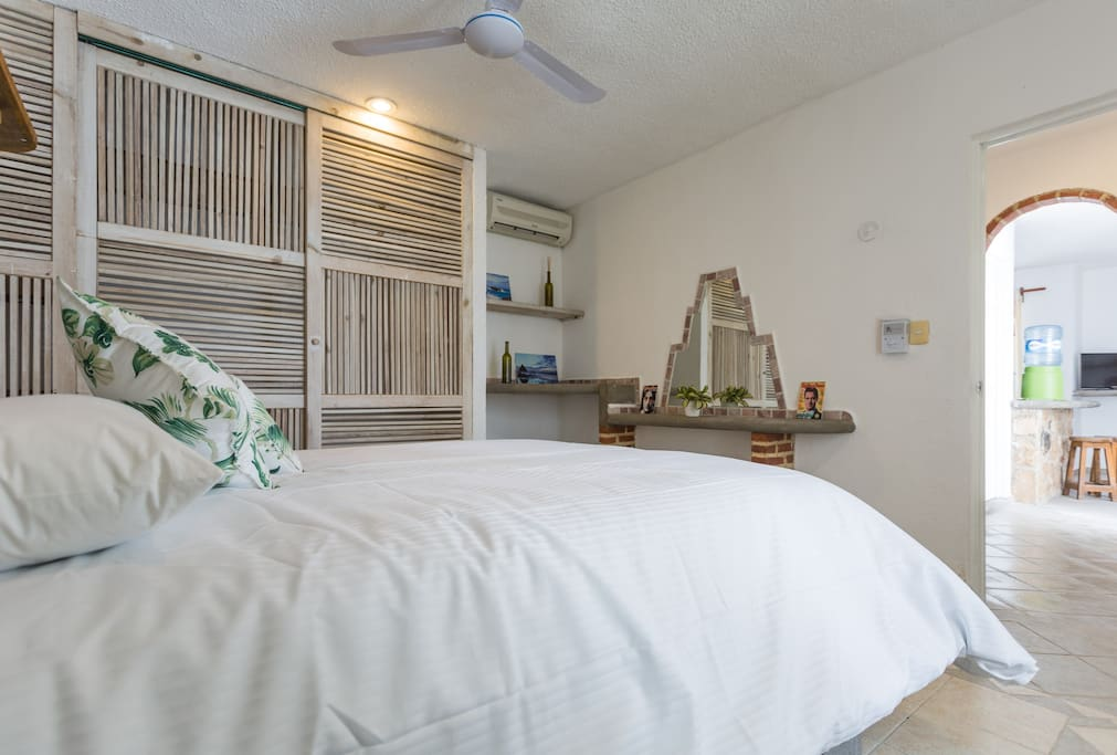 Master bedroom with fabulous queen size bed, air conditioner, ceiling fan and spacious closet