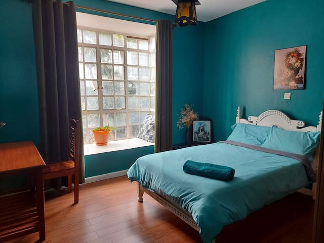 Secondary bedroom with a comfortable double bed with a view of the green lush outdoors.  Large bay window that can be used as a reading nook