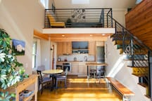 The downstairs main area is an open & airy kitchen and dining room.  Stairs lead up to the loft area.