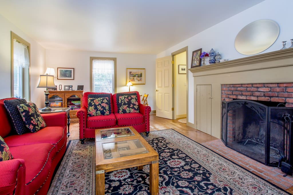 The living room includes comfortable seating and a wood-burning fireplace.