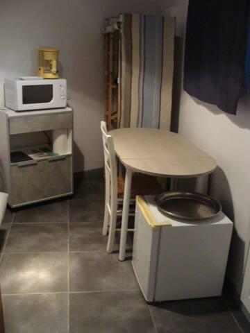 entrée de la chambre avec table à manger, petit frigo, micro-ondes, cafetière, penderie et le nécessaire en verres / couverts pour 2 personnes