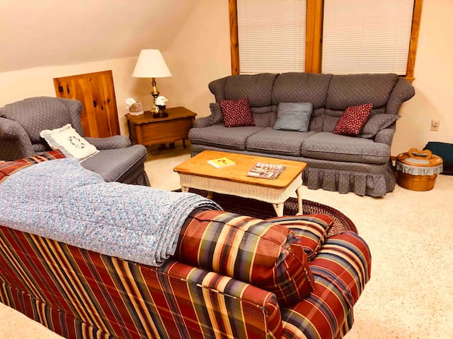 """This bonus room above the garages is huge-perfect for games and for the """"kids sleeping area."""" It boasts a TV, games, great view of lake, couch, single sleigh bed, desk, table and air mattresses."""