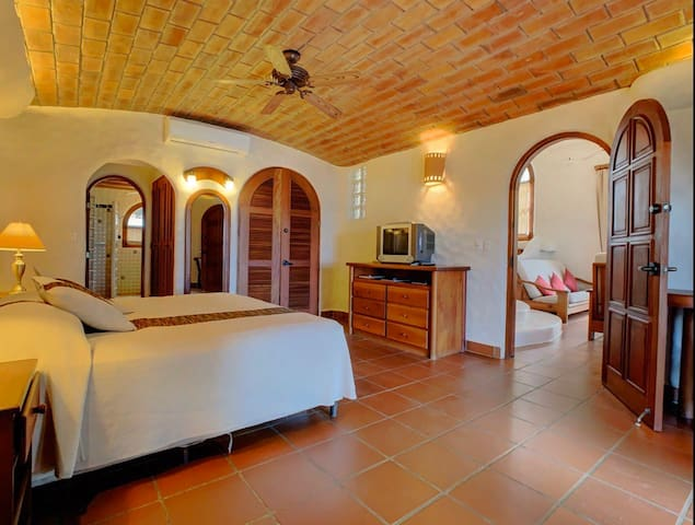 """The downstairs """"Bear Cave"""" master bedroom. This space has its own balcony entrance and private bathroom. The brick ceilings keep temperatures cool and the bedroom cozy."""