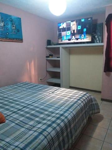 Dormitorio con cama king y tv
