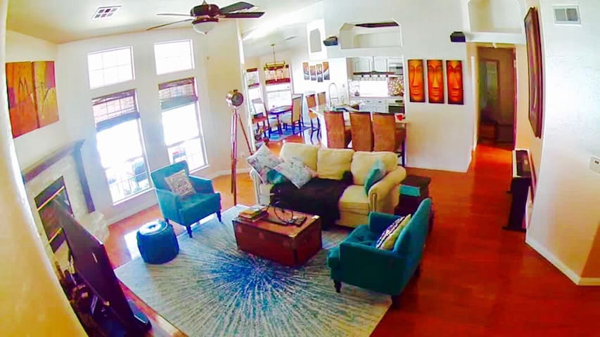 Wide view of the chic, cozy living room space with a relaxing, open full view of the pool and garden